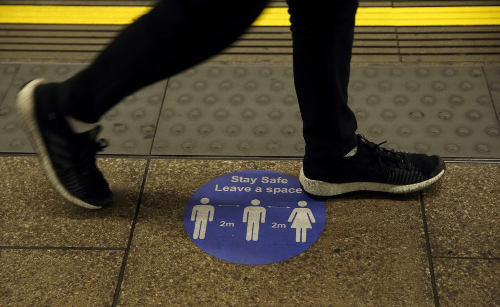 A sign on the platform at Embankment Underground station tells commuters that they need to observe a two-metre gap as they travel. This will now change to a one metre gap.