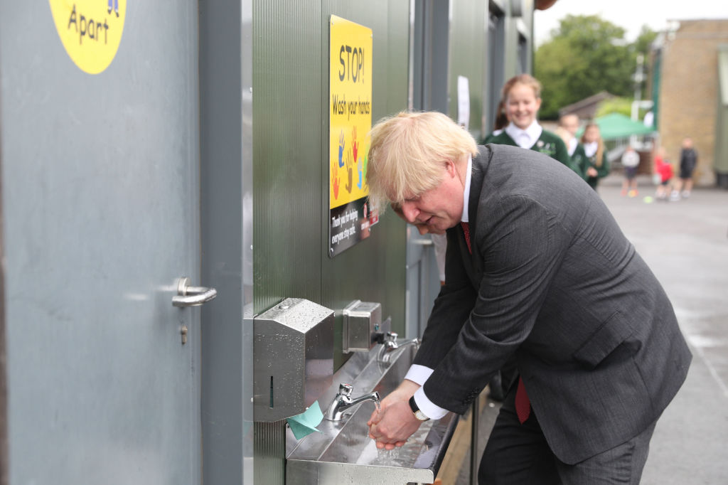 Prime Minister Boris Johnson washes his hands at a sink in the playground during a visit to Bovingdon Primary School in Bovingdon, Hemel Hempstead, Hertfordshire on June 19, 2020