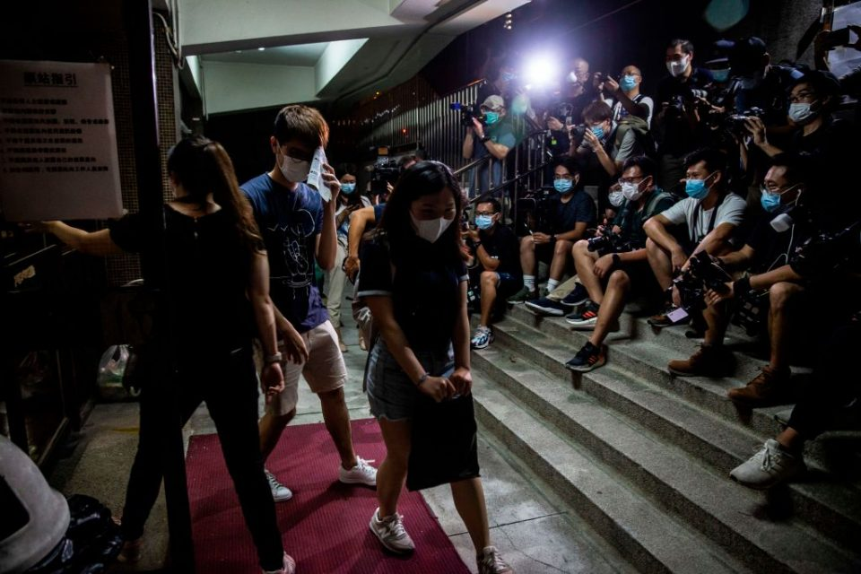 A women passes members of the mediaas she leaves a venue after voting in Hong Kong on June 20, 2020, during a vote organised by selection of pro-democracy unions to ask members if they will participate in a city wide strike and if they supported China's plans to impose a new national security law