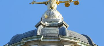 The statue of justice stands on the copu