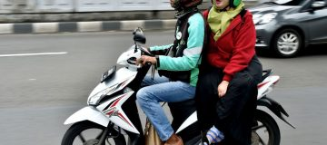 A GrabBike rider transports a passenger in Jakarta in 2017