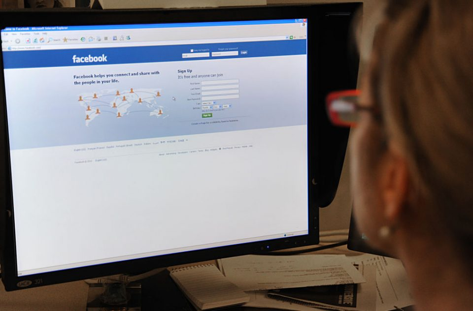 A woman prepares to log on to the Facebo