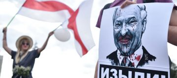 """A man holds a picture of the Belarus President Alexander Lukashenko reading """"Go away!"""" during a protest rally against police violence during recent rallies of opposition supporters, who accuse strongman Alexander Lukashenko of falsifying the polls in the presidential election"""