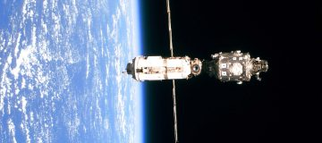 The International Space Station (Iss Is Backdropped Against The Blue And White Horizon Scene Of Ear