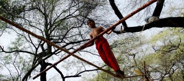 A young Indian trapeze artist walks the...