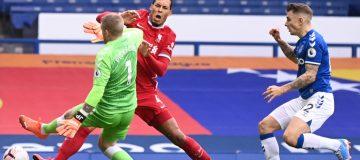 Jordan Pickford of Everton tackles Liverpool's Virgil van Dijk