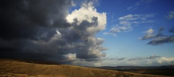 blue sky behind storm clouds in countryside