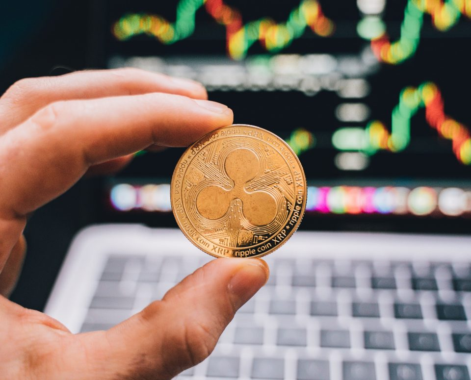 Ripple XRP coin in front of laptop screen